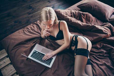 Oben über dem Blickwinkel von ihr, sie sieht gut aus, anmutig, kurvig, luxuriös, atemberaubend, wunderschön, weiblich, hübsche Dame, die auf dem Bett liegt und mit ihrem Freund auf Bettwäsche plaudert Standard-Bild