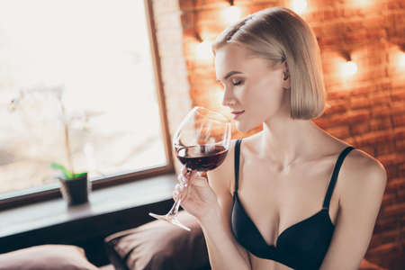 Close up side profile photo overjoyed beautiful tenderness gorgeous, she her lady hold arms hands alcohol beverage glass eyes closed romance date sit sheets honeymoon bikini boudoir room indoors