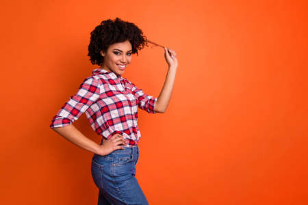 Profile side view portrait of her she nice attractive lovely cheerful cheery flirty coquettish wavy-haired lady playing with curls isolated on bright vivid shine orange background