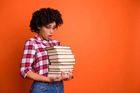 Close up side profile photo beautiful she her model lady oh no expression, open mouth hold arms hands many books examination stupor wear casual checkered plaid shirt isolated bright orange background