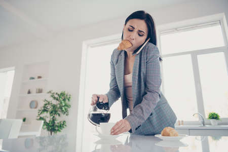 Close up photo beautiful tired she her lady pour cup hot beverage croissant inside, mouth late job quickly speak tell say telephone formal-wear checkered plaid costume bright white kitchen indoors