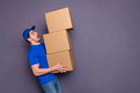 Close up photo profession specialist he him his delivery boy hold strong hands, large big heavy parcel boxes flat move exhausted stressed wear blue t-shirt cap jeans denim isolated grey background