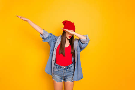 Portrait of cute teenager, hide face raise hands isolated over yellow bright background