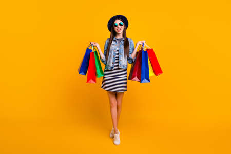 Full length body size view photo positive cheerful satisfied lady youth hold hand package colorful black friday candid stylish eyewear eyeglasses skirt striped denim clothes isolated yellow background