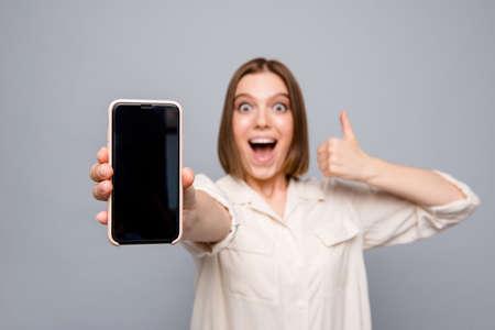 Primo piano foto pazza bella lei la sua signora mani braccia telefono alzare pollice su urlare urlare gridare consigliare cliente acquistare acquirente dispositivo prezzo basso indossare casual camicia bianca isolato sfondo grigio