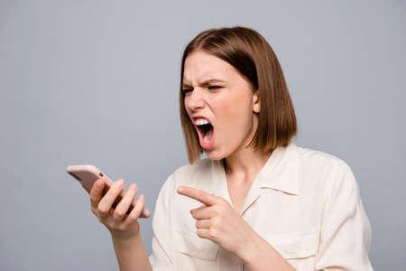 Nahaufnahme Foto wütend erstaunlich schön sie ihre Dame Händchen halten Arme Telefon hören unerwartete schlechte Nachrichten wildes Gebrüll Freund unzufrieden Wahnsinn tragen lässiges weißes Hemd isoliert grauer Hintergrund