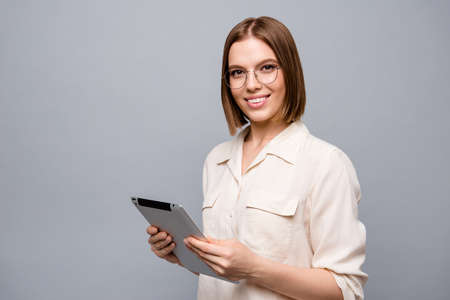 Close up side profile photo beautiful attractive she her business lady chief e-book hands arms reader data startup novelty interested curious wear specs casual white shirt isolated grey background Фото со стока