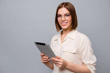 Close up side profile photo beautiful attractive she her business lady chief e-reader hands arms reader data startup novelty interested curious wear specs casual white shirt isolated grey background Фото со стока
