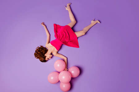 Full length body size inverted reverse view of her she nice charming attractive lovely slim fit thin cheerful lady in short cocktail dress holding balls isolated over violet pastel background