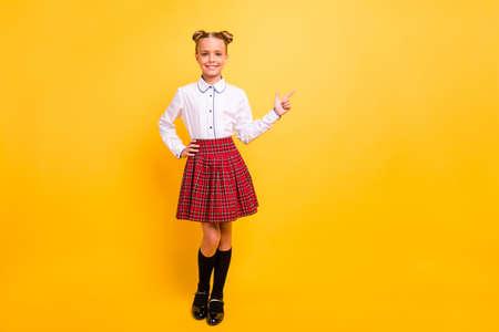 Ganzkörperansicht Porträt eines hübsch aussehenden, attraktiven, fröhlichen, fröhlichen, selbstbewussten Mädchens im Teenageralter in weißem Hemd, das zur Seite zeigt Werbeanzeige einzeln auf hell leuchtendem gelbem Hintergrund