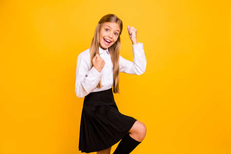 Portrait of her she nice-looking attractive cheerful cheery glad straight-haired pre-teen girl having fun rejoicing great news attainment isolated, on bright vivid shine yellow background Stock Photo