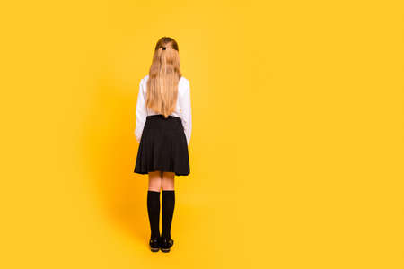 Rear back behind full length body size view of her she nice-looking, attractive straight-haired pre-teen girl standing still isolated on bright vivid shine yellow background