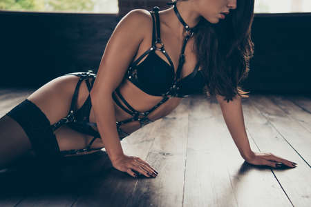 Cropped portrait of nice exquisite adorable charming attractive winsome, sportive shape figure wavy-haired lady wearing swordbelt teasing posing lying on floor at loft interior wood Stock Photo