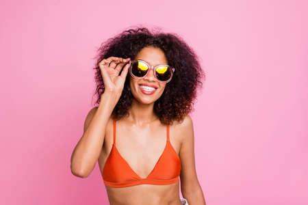 Cerrar foto divertida hermosa ella su piel oscura dama con dientes radiante sonrisa ir junto al mar playa deseo bronceado exótico resort de isla usar sol especificaciones natación traje naranja sujetador aislado fondo rosa
