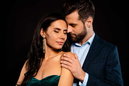 Close up photo rich pair classy she her chic eyes closed enjoy he him his hold touch shoulders tenderness piggyback pose wear blue plaid costume jacket velvet green dress isolated black background