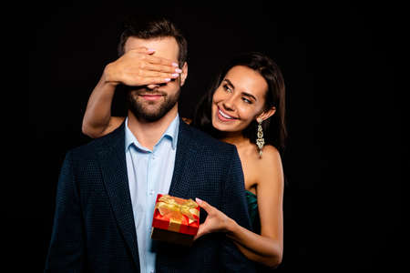 Portrait of nice-looking attractive lovely luxurious fascinating cheerful cheery dreamy two person lady closing covering guys eyes prepared expensive package isolated over black background Archivio Fotografico