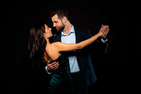 Close up back rear behind photo beautiful she her wife he him his husband mrs mr married spouse hold hands tango slow dance position gentle wear costume jacket green dress isolated black background Stock Photo