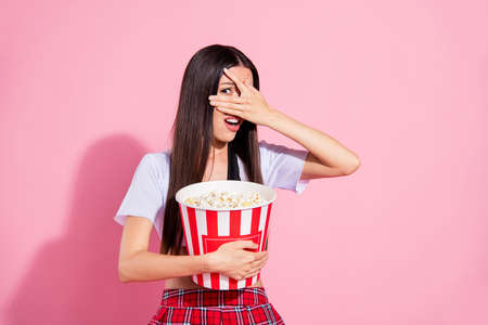 Photo of amazed lady hold hands popcorn container hide face scary movie wear white top red skirt isolated pink background Standard-Bild
