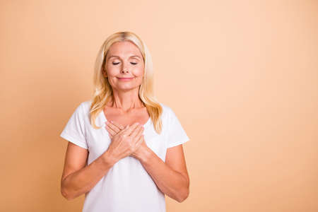 Photo of amazing aged lady eyes closed hands chest overjoyed pretty wear white casual t-shirt isolated pastel beige background