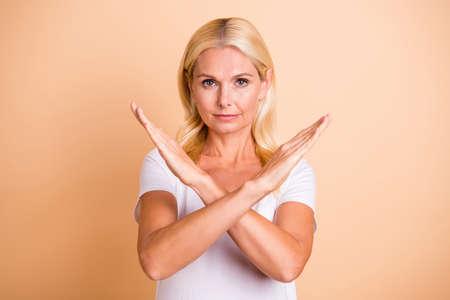 Foto van gekruiste damesarmen nee, je gaat niet door het symbool, draag een wit casual t-shirt geïsoleerd pastelbeige achtergrond Stockfoto