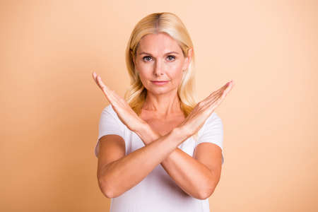 Photo of lady arms crossed no you will not pass through symbol wear white casual t-shirt isolated pastel beige background