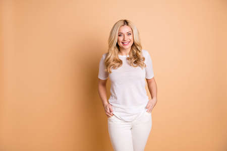 Close up photo amazing beautiful she her lady hands arms pockets nice toothy smile kindhearted easy-going person sincere wear casual pants trousers white t-shirt isolated beige pastel background