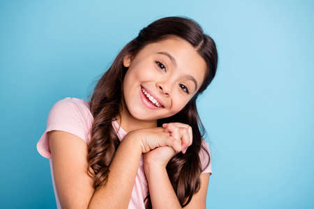 Close up photo cute charming kid place hands palms chest neck ask please surprise birthday she want wait expect feel optimistic wear modern clothing isolated blue background Stock Photo