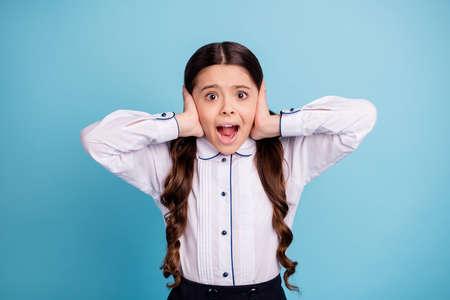Photo of pretty school lady hands fingers hide ears noisy classroom yelling classmates wear white shirt isolated blue background Standard-Bild