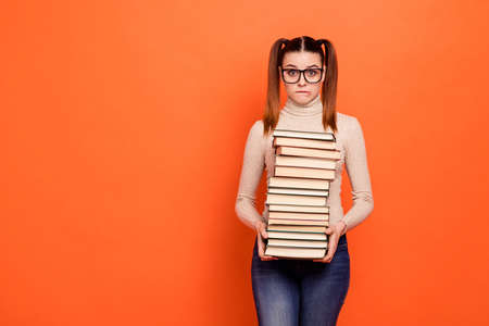 Close up photo beautiful she her lady pretty hairstyle bite lip oh no expression hold arms hands many books eyes full fear examination wear casual pastel pullover clothes isolated orange background