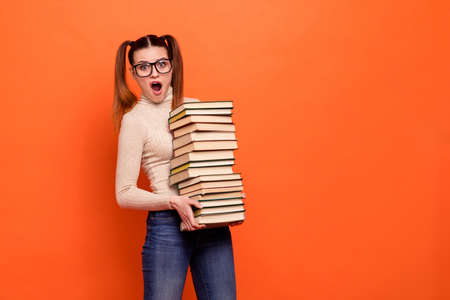 Close up photo beautiful she her lady funny pretty hairstyle yelling oh no open mouth hold arms hands many books prepare examination wear casual pastel pullover clothes isolated orange background