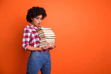 Close up side profile photo beautiful she her model lady oh no expression open mouth hold arms hands many books examination stupor wear casual checkered plaid shirt isolated bright orange background 免版税图像