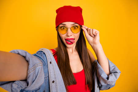 Close up photo of cute trendy teen make faces grimacing touch eyewear eyeglasses isolated over yellow background