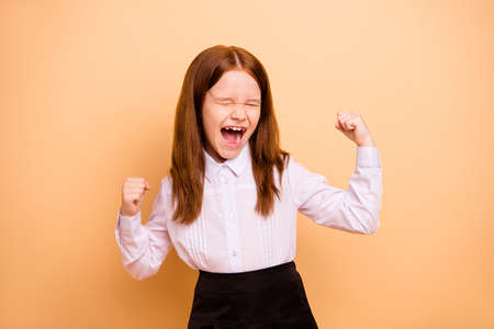 Portrait of nice attractive lovely crazy cheerful cheery overjoyed pre-teen girl great cool news dream attainment accomplishment rejoicing isolated over beige pastel background Banque d'images