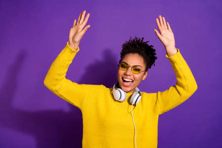 Portrait of cheerful funny millennial scream shout raise palms hands have earphones eyewear eyeglasses isolated over violet background