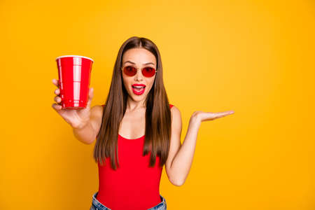 Close up photo of beautiful lady bright lips hold hand alcohol beverage shocked good taste wear sun specs red body tank-top denim shorts Stock Photo