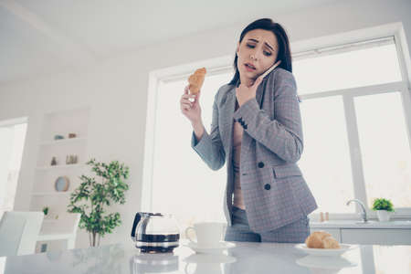 Close up photo beautiful tired she her lady cup pot hot beverage table croissant hand arm late job quickly speak tell say telephone formal-wear checkered plaid costume bright white kitchen indoors Фото со стока