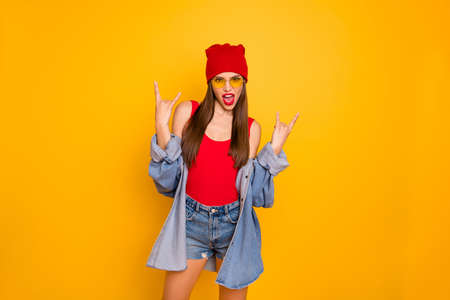 Photo of funky lady bright lips nice colorful look visit rock concert famous group band hand show horns symbol wear sun specs red body tank-top denim blazer Stock Photo