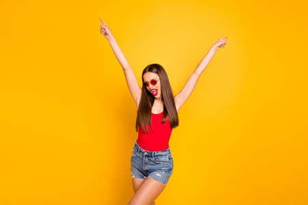 Close up photo of beautiful lady plump bright lips overjoyed childish person hands raised up wear sun specs red body tank-top denim shorts