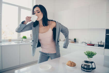 Close up photo beautiful she her lady hot beverage swallow sip croissant table late job quickly dressing jacket blazer exhausted formal-wear checkered plaid costume bright white kitchen indoors