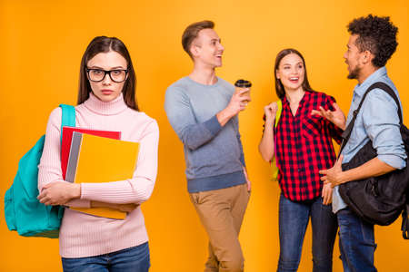 Portrait of nice-looking attractive cheerful cheery company discussing news and expelled odd unwanted clever smart girl excluded from them isolated over bright vivid shine yellow background