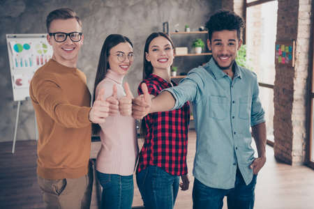 Close up photo positive cheerful excited entrepreneur marketers content enjoy excellent work showing like fine sign denim jeans plaid clothes shirt sweater pullover stand interior industrial loft Imagens
