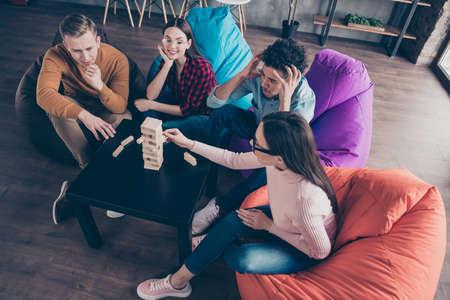 Sopra la vista dall'alto di simpatici ragazzi allegri e attraenti dipendenti del responsabile dello sviluppo seduti su sedie a sacco che fanno puzzle difficile nella postazione di lavoro interna del loft industriale