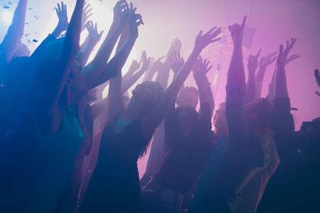 Close up photo of many birthday party people dancing clubbing purple lights confetti fog nightclub hands raised shiny formal-wear