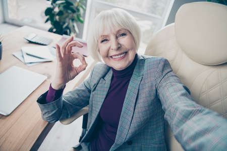 Close up photo of aged business lady day off make take selfies okey symbol great job sit office chair wear plaid costume suit jacket Stock Photo
