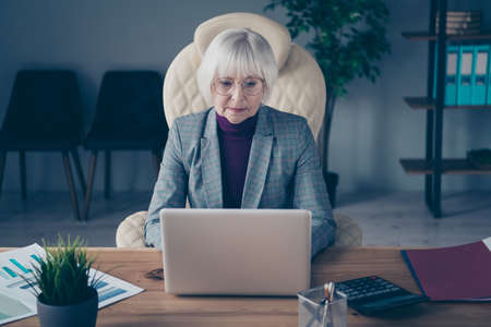 Photo of aged business lady head big organization writing report sitting modern chair notebook table wear specs plaid costume jacket