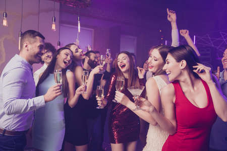 Portrait of nice adorable elegant fascinating glamorous chic smart attractive cheerful cheery positive dreamy glad ladies and guys having fun birthday rest relax nightlife at fogged lights nightclub