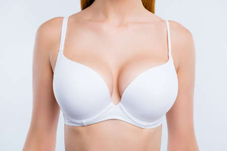 Cropped close-up portrait of nice attractive adorable girl chest after uplift injection wearing white bra isolated over light gray background