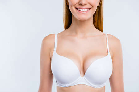 Cropped close-up portrait of nice confident attractive lovely cheerful cheery blonde girl chest after uplift injection wearing bra isolated over light gray background