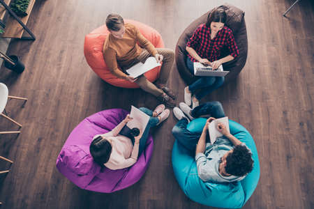Top above high angle view of busy stylish guys junior managers sitting on bag chair preparing financial annual marketing report at industrial wooden loft interior workplace workstation