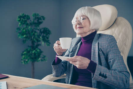 Closeup photo of aged business lady hands hot beverage mug eyes closed overjoyed sit office chair wear specs costume suit jacket